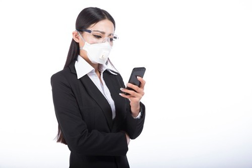 Black hair girl with a mobile phone in her hand and pollution mask on her face.
